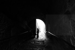 Echoes, Part 1 (Elios.k) Tags: horizontal outdoors people two man silhouette shadow contrast entrance archaeologicalsite gate arch arc architecture unescoworldheritagesite pompeiiarchaeologicalpark parcoarcheologicodipompei light path stone columns wall tunnel blackandwhite mono monochrome bw travel travelling february 2018 vacation canon 5dmkii camera photography pompeii ancient roman city campania naples napoli italy europe