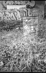 metaal storage silo, round trash can, graffiti, River District, Asheville, NC, Nikon LF352AF, Kodak Tri-X 400, HC-110 developer, 4.1.19 (steve aimone) Tags: silo metal trashcan graffiti urbanlandscape urbandecay riverdistrict asheville northcarolina nikonl35af2 kodaktrix400 hc110developer pointandshoot 35mm 35mmfilm film monochrome monochromatic blackandwhite