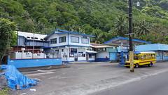 The barber shop, a market, and an aiga (local bus) along the main drag