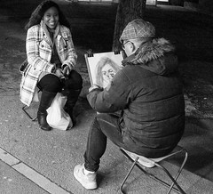 There Is Something In My Eye (tcees) Tags: quaibranly paris france x100 fujifilm finepix urban streetphotography street stool bw mono monochrome blackandwhite man woman people pavement sidewalk artist painter seat cap smile caricaturist caricature clips board paper bag night dark coat