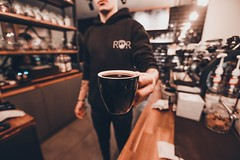 man in black pullover hoodie handing filled black ceramic mug - Credit to https://myfriendscoffee.com/ (John Beans) Tags: coffee cafe coffeebeans shopbeans espresso coffeecup cup drink cappucino latte
