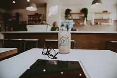 black framed eyeglasses beside glass cup on white wooden table - Credit to https://myfriendscoffee.com/ (John Beans) Tags: coffee cafe coffeebeans shopbeans espresso coffeecup cup drink cappucino latte