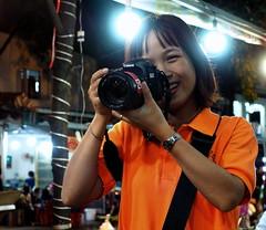 Photographer's Smile (RJAB2012) Tags: hochiminh saigon vietnam vietnamese photographer smile asian beautiful girl orange canon night flare olympus 100v10f