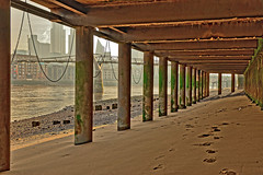 Under the Boardwalk (Croydon Clicker) Tags: river water thames millenniumbridge tower skyscraper chain pillars sand footprints foreshore beach bridge london