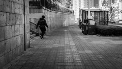 Coming from nowhere... (Go-tea 郭天) Tags: qingdao shandong républiquepopulairedechine wall pavement sidewalk lines stairs hidden hide secret arise arising surprised exit entry man walk walking alone lonely sun sunny shadow cold winter unexpected street urban city outside outdoor people candid bw bnw black white blackwhite blackandwhite monochrome naturallight natural light asia asian china chinese canon eos 100d 24mm prime back backside alley empty garbages motorbike