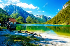 small building at a beautiful lake surrounded by stunning mountain landscape. (a_bmohamedm) Tags: mountain summer water nature lake green travel rock sky landscape house building mountains beautiful park tree outdoors reflection peak alpine blue scenic hiking national grass scenery tourism white peaceful cliff glacier serenity trekking wilderness quiet wild rocky beauty top valley alps ridge tranquil panorama range stone cloud instagram filter destination