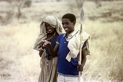 77-289 (ndpa / s. lundeen, archivist) Tags: nick dewolf color photograph photographbynickdewolf 1976 1970s film 35mm 77 reel77 africa northernafrica northeastafrica african ethiopia ethiopian centralethiopia southwesternethiopia people localpeople woman youngwoman man youngman weapon spear necklace necklaces grass grassy landscape terrain headcovering bag sack burlapsack