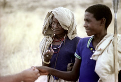 77-291 (ndpa / s. lundeen, archivist) Tags: nick dewolf color photograph photographbynickdewolf 1976 1970s film 35mm 77 reel77 africa northernafrica northeastafrica african ethiopia ethiopian centralethiopia southwesternethiopia people localpeople woman youngwoman man youngman weapon spear necklace necklaces grass grassy landscape terrain headcovering bag sack burlapsack