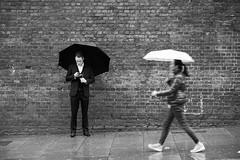 Rain (MaxGoe) Tags: street london walking cell phone rain umbrella black white weather brick wall city england beautifulexpression hurry