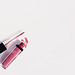 Nail polish bottle and drop on white background