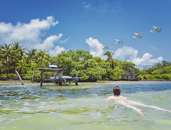 Playing out in the water in front of our place... - Caye Caulker Belize (Jonmikel & Kat-YSNP) Tags: belize ocean vacation water shore dock trees plane airplane takeoff swiming