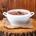 Soup-Solyanka with smoked meat on the stump of white tureen