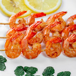 Wooden skewers with tails of grilled shrimp with lemon circles on a white plate thumbnail