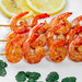 Wooden skewers with tails of grilled shrimp with lemon circles on a white plate