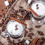 Top view of coffee with cream, coffee beans and spices on burlap thumbnail