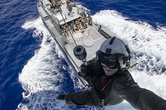 Naval Air Crewman is lowered to a Mark VI patrol boat from an MH-60S Sea Hawk helicopter.