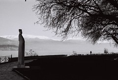 Static Observers (Elios.k) Tags: horizontal outdoors people oneperson walk walking pedestrian distance silhouette trees planetree platanus bare branches lake lakepamvotis lakefront path water mountains sculpture art artinpublic theodorospapagiannis workofart stone marble couple statue sky blackandwhite mono monochrome bw travel travelling february 2018 vacation canon camera photography ioannina epirus greece ιωάννινα ελλάδα ήπειροσ europe dark film analoguephotography scannedfilm analogfilm grain canona1 a1 analogcamera kodaktrix trix400