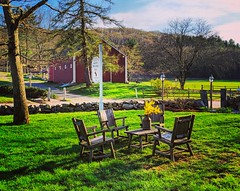 beautiful spring evening (ekelly80) Tags: massachusetts marlborough april2019 spring newengland inn longfellowswaysideinn ground light evening sunset glow table chairs flowers forsythia barn red shadows beautiful