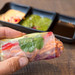 Hand holds a summer roll filled with avocado, mango, paprika, red cabbage, carrots and rice noodles with various sauces in the background