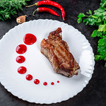 Delicious roasted meat with berry sauce, herbs and chili on a black background thumbnail
