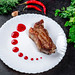 Delicious roasted meat with berry sauce, herbs and chili on a black background