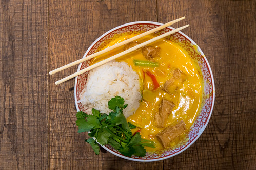 Veganes, asiatisches Essen im coa-Restaurant: Kokos-Curry mit Tofu, Paprika, Pilzen, Süßkartoffeln, Reis, Spinatblättern, in einer Schüssel mit Essstäbchen