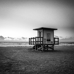 Before Dawn (tim.perdue) Tags: cocoa beach florida merritt island 2019 travel panasonic gx7 lumix 1232mm 30100mm mirrorless micro four thirds mft m43 43 ilc evil ocean sea shore shoreline atlantic water sky clouds sand surf waves sunrise sunup dawn daybreak early morning sun lifeguard station shack black white bw monochrome blackandwhite mono square instagram