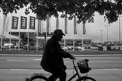 Dębica Cycling past Raj IMG_1668.jpg b.jpg bw (david.neville2776) Tags: dębica podkarpackie cyclist raj shopping centre bw
