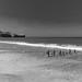 Beach with breakwater posts and dark sky.