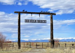 Ranch Country (Patricia Henschen) Tags: southriverroad alamosa colorado riovega ranch sign entrance rural countryside roadside unpaved mountain mountains sangredecristo sanluisvalley clouds snow capped gate fence road pathscaminhos