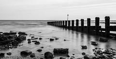 Rocky Beach (Colin Freeman Photography) Tags: beach wales groyne sand rock sea coast landscape wind farm bw black white nikon d750 fx 2470 colwynbay cloud mono timber wood reflection shadow
