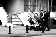 Babysitting (milenabajceta) Tags: street photography bw babies men babysitting baby carriage building fence daylight podgorica montenegro europe