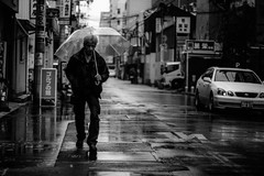 blue day (tomorca) Tags: man rain umbrella street monochrome blackandwhite fujifilm xt2