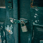 A lock on an old and rustic green door with paint peeling off thumbnail