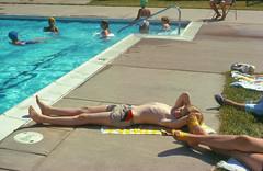 Tom on the towel, June 1981 (Apotheoun) Tags: boy blond swimsuit legs towel 1981 apotheoun pool sunning reclining pale tan grass cement swimming