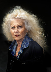 Portrait (D80_532394) (Itzick) Tags: telavivmar2019 candid color colorportrait woman blonde longhair face facialexpression streetphotography blackbackground earrings necklace d800 itzick