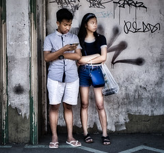 Watching and Checking (Beegee49) Tags: street people checking messages man woman look out luminar sony a6000 bacolod city philippines asia