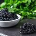Black caviar on a dark stone background with greens