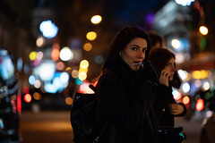 (graveur8x) Tags: woman candid street potrait city paris france bokeh colours urban look eyecontact smile phone mobilephone call people outside outdoor dof lights dark night frankreich streetphotography buildings sony sonya7iii sonyilce7m3
