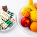 Tablets and fresh fruit on white background. The concept of choosing between a healthy diet and treatment