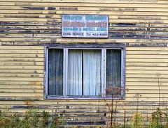 Charlie Wheeler Heating Service, Hancock, Maine, USA (Spencer Means) Tags: dwwg building abandoned charliewheeler heating service business sign old faded weathered window wood hancock me maine