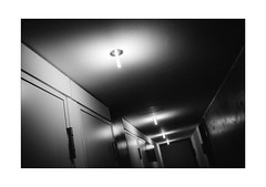 Claustrophobic Corridor (Thomas Listl) Tags: thomaslistl blackandwhite biancoenegro noiretblanc monochrome 35mm indoor corridor vanishingpoint light lamps contrast shadow dark grain wall angle diagonal lines geometry graphical