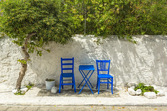 Take a Seat (Ramon Quaedvlieg Photo) Tags: greece samos chair chairs table green tree plant blue nature outdoor streetpgotography streetscene street streetlife sit relax pythagorion light white plaster wall rocks