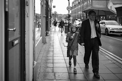 Dad & Daughter Walking in The Rain (Foto John) Tags: leica leicammonochrom246 leicammonochromtyp246 summiluxm35mmƒ14asphfle rangefinder streetphotography people girl man father daughter street cars blackwhite blackandwhite blackandwhitethatsright monochrome rain umbrellas crouchend london uk