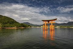 Itsukushima Floating Torii - Miyajima Island (Japan) (Andrea Moscato) Tags: andreamoscato giappone japan asia japanese 日本 nihon nippon asian light luce green shadow ombre prefecture attraction ombra site national nature natura natural naturale landscape paesaggio day white sky cielo view vivid vista scenic blue parco park trees history historic ancient treasure wood art architecture monument tree brilliant water silhouette sea seascape seashore beach torii gate bay hiroshima unesco world heritage island isola seto inland setonaikai riflesso reflection tide sand orange mountain hill nuvole clouds deep
