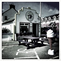 Lick'd (Explored) (Julie (thanks for 9 million views)) Tags: kilmorequay bench takeaway ireland irish wexford building bw monochrome squareformat table seaside iphonese 100xthe2019edition 100x2019 image55100 street icecreamcone advertising door window hbm benches windows wall hww inexplore