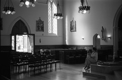Cathedral of St Patrick & St Joseph  (FP4+) (Harald Philipp) Tags: architecture building structure urban citycenter city church catholicchurch worship stainedglass window lamps destination travel island haraldphilipp kodakretina retinaiiic fp4 ilford 35mm 135 film grain analog filmphotography rangefinder primelens southpacific newzealand auckland pews chairs woman infant baby baptismal door statue jesus softfocus