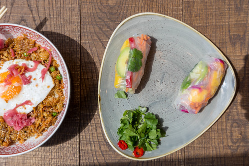 Flatlay of the vegetarian Fried Sunrice meal and two vegan Rainbow Summer Rolls in the coa Wok & Bowls restaurant in Cologne