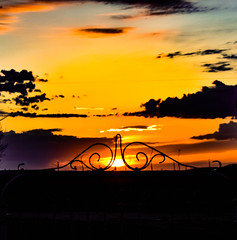 Through the gate (darletts56) Tags: sky blue yellow orange red grey cloud clouds silhouette black gold golden sun sunset prairie saskatchewan canada pole poles tree trees lamp light lights wire wires gate line lines lamps building buildings roof tops