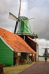 Windmills of Zaanse Schans (Brett of Binnshire) Tags: manipulations historicalsite on1raw zaandam netherlands museum zaanseschans locationrecorded northholland windmill bicycle path door cobbles river